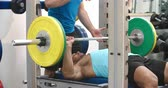 instrutor : Trainer assisting man bench pressing barbells at a gym