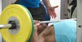 грудь : Trainer assisting man bench pressing barbells at a gym