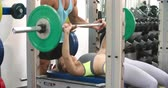 assistance : Young woman chest pressing barbells with a trainer at a gym Stock Footage