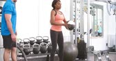 conselho : Young woman doing squats in a gym with advice from a trainer