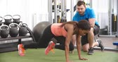 fitness : Young woman working out in gym under supervision of trainer