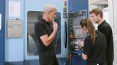 maquinaria : Two Apprentices Working With Engineer On CNC Machinery Stock Footage