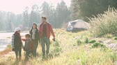 recreativa : Parents on a camping trip with two kids walking near a lake