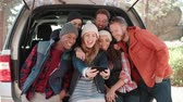 nativo : Group of six friends take a selfie in an open car hatchback