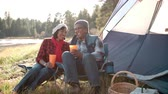 namiot : Senior black couple on a camping trip relax outside tent