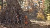 urlop : Five young children playing together leave a hut in a forest Wideo