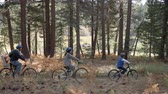 pan left : Family cycling through a forest together, left to right pan Stock Footage