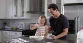 misturando : Caucasian girl and dad have fun preparing cake mix mix, shot on R3D