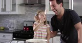 misturando : Girl putting cake mix mix on dad's nose while they bake together, shot on R3D