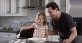 misturando : Caucasian girl spooning out cake mix mix for baking with her dad, shot on R3D