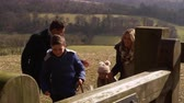 olhando para baixo : Family with dog walking through gate in open countryside, shot on R3D