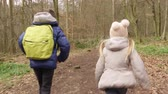 urgente : Back view of two children running on a path through a forest, shot on R3D