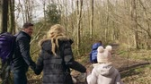 handheld : Family of four and pet dog walking through forest, handheld, shot on R3D