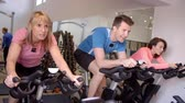 recreativa : Side view of a spinning class on exercise bikes at a gym Vídeos