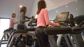 lustro : Three woman exercise on equipment at a gym, low angle Wideo
