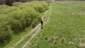 vysoký úhel : Aerial Shot Of Woman Walking Along Path In Countryside Dostupné videozáznamy