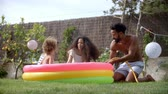 à beira da piscina : Family Having Fun In Garden Paddling Pool