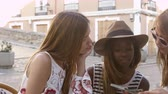 inteiro : Three female friends read guidebook outside a cafe, Ibiza