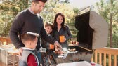 espanha : Family barbecuing on a deck in the forest