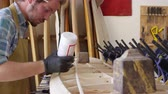 tesař : Man Glueing Custom Surfboard In Workshop Shot