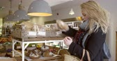 consumismo : Woman Shopping For Organic Bread In Delicatessen