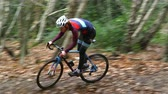 Young man cross-country cycling between trees in a forest Stock Footage