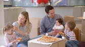 движение : Family Celebrating Moving Into New Home With Pizza Стоковые видеозаписи
