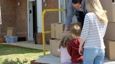 propriedade : Family Unpacking Moving In Boxes From Removal Truck Stock Footage