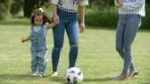 chutando : Mum and friends kicking a ball outdoors with young daughter