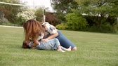 prato : Young girl lying on grass with ball playing with her mother