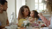 Couple, young girl and adult friends talk at kitchen table Stock Footage
