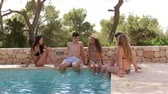 à beira da piscina : Teenage friends sitting at the edge of a swimming pool talking
