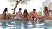 pessoa : Teenage friends sitting at the edge of a swimming pool talking