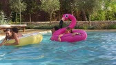 guarda chuva : Teenage friends have fun with inflatables in a swimming pool Vídeos
