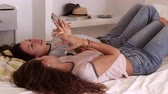 wi fi : Teenage girls lying on bed talking and using smartphone, shot on R3D