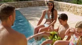 traje : Family On Vacation Relaxing By Outdoor Pool