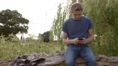 sentar se : Young man sitting on a fallen tree messaging with smartphone Stock Footage