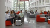выше : Students socialise in the busy lobby of a modern university