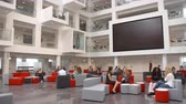 выше : Students sit talking under AV screen in atrium at university Стоковые видеозаписи