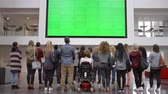 выше : Students applaud a big screen in university foyer, back view
