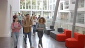 выше : Students walk through the foyer of a modern university