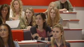 выше : Handheld tilt shot of students in university lecture theatre