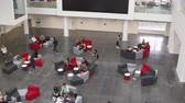 выше : Overhead handheld tilt shot of university atrium and lobby