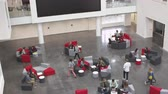 выше : Overhead handheld tilt shot of university atrium and busy lobby Стоковые видеозаписи