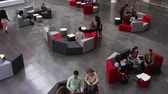 campus : Elevated pan shot of students in busy university lobby area Stock Footage