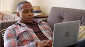 em linha : Man Relaxing On Sofa At Home Using Laptop