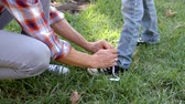 tkanička : Father tying his sons shoelace in a park, low section