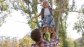 lente : Dad holding his young daughter in the air in a park