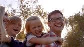 piggyback : Young white family having fun piggbacking in a park Stock Footage