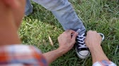 шнурки : Father tying his sons shoelace in a park Стоковые видеозаписи